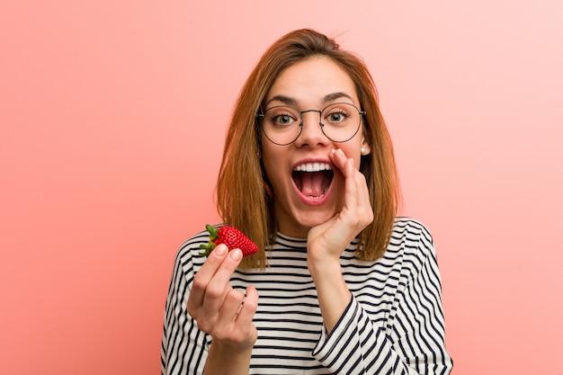 Jovem mulher segurando uma morango gritando animado para a frente.