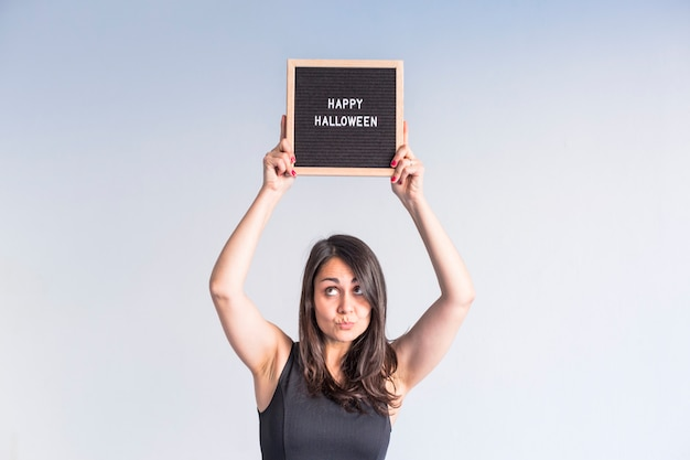 Jovem mulher segurando uma placa de carta vintage preto com sinal de feliz dia das bruxas. estilo de vida em ambientes fechados