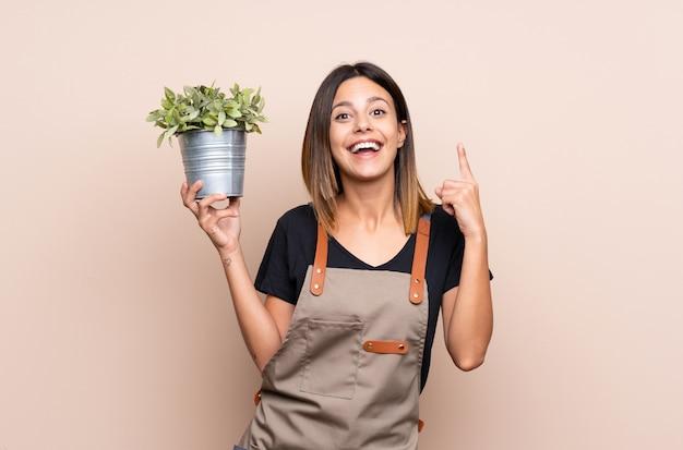 Jovem mulher segurando uma planta apontando para cima uma ótima idéia