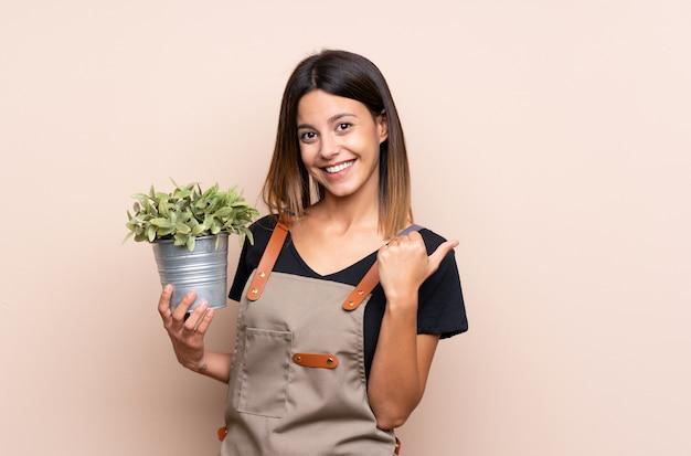 Jovem mulher segurando uma planta apontando para o lado para apresentar um produto