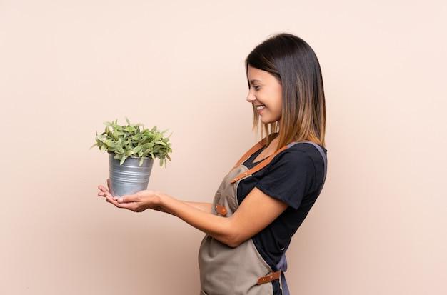 Jovem mulher segurando uma planta com expressão feliz