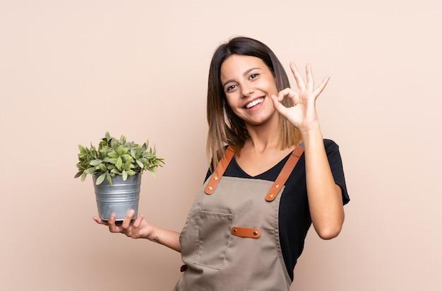 Jovem mulher segurando uma planta mostrando sinal de ok com os dedos