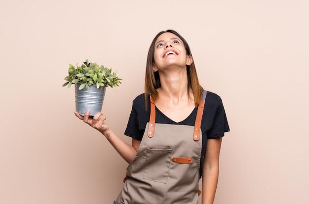 Jovem mulher segurando uma planta olhando para cima enquanto sorrindo