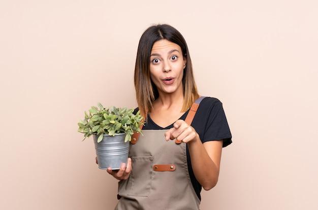 Jovem mulher segurando uma planta surpreendida e apontando a frente
