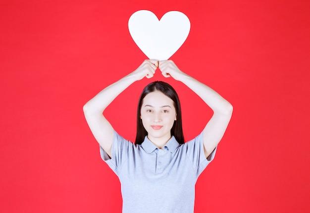 Jovem mulher segurando uma prancha em forma de coração no topo da cabeça