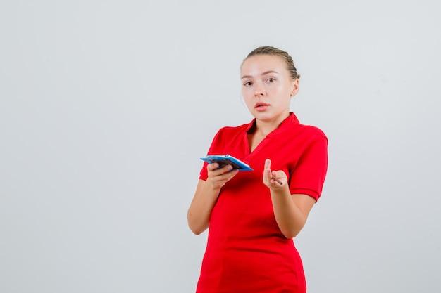 Jovem mulher segurando uma prancheta e um lápis com uma camiseta vermelha e parecendo confusa