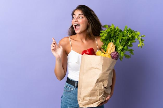 Jovem mulher segurando uma sacola de compras, apontando o dedo para o lado e apresentando um produto