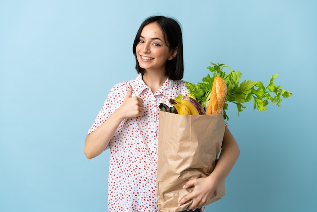 Jovem mulher segurando uma sacola de compras de supermercado e fazendo um gesto de polegar para cima