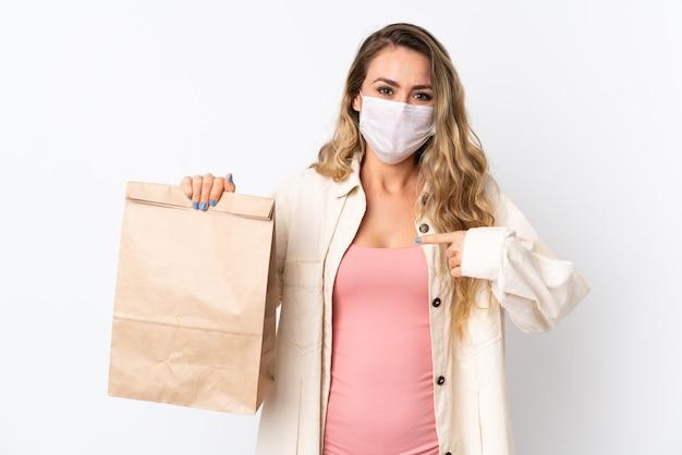 Jovem mulher segurando uma sacola de compras de supermercado isolada na parede branca com expressão facial surpresa