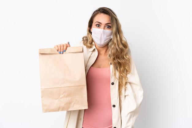 Jovem mulher segurando uma sacola de compras de supermercado isolada no branco com expressão facial surpresa e chocada
