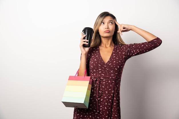 Jovem mulher segurando uma sacola pequena e um copo de bebida na parede branca.