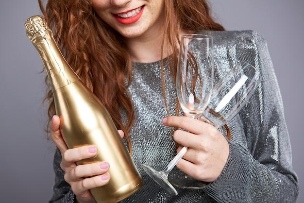 Jovem mulher segurando uma taça de champanhe e uma garrafa