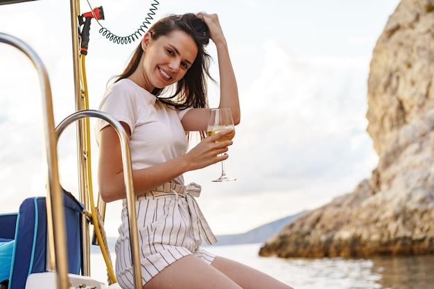 Jovem mulher segurando uma taça de vinho e sentada no convés de um iate à vela