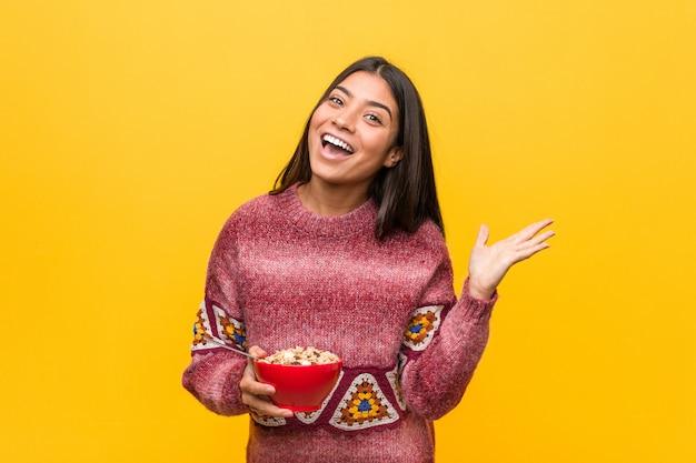 Jovem mulher segurando uma tigela de cereais comemorando uma vitória ou sucesso