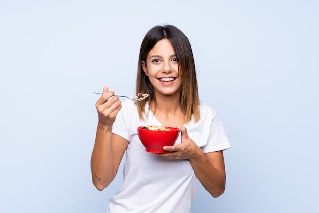 Jovem mulher segurando uma tigela de cereais
