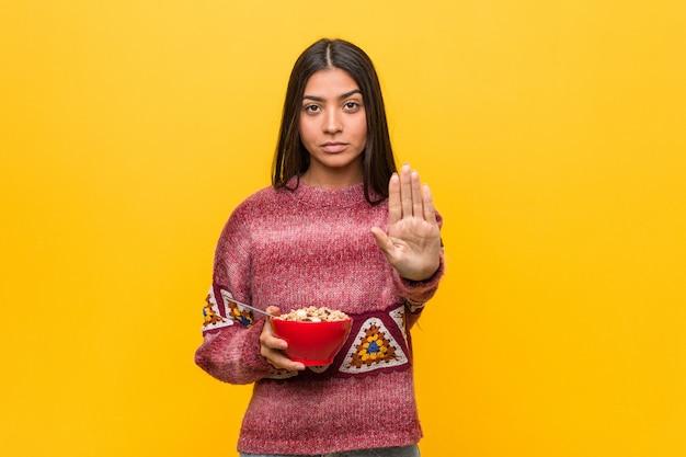 Jovem mulher segurando uma tigela de cereal em pé com a mão estendida, mostrando o sinal de stop, impedindo-o