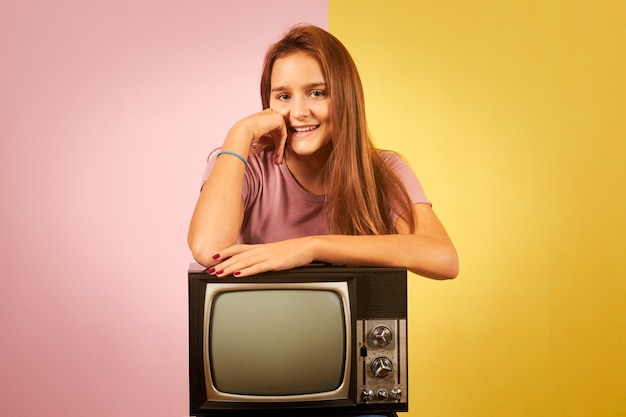 Jovem mulher segurando uma velha tv retrô sentada contra um fundo amarelo e rosa