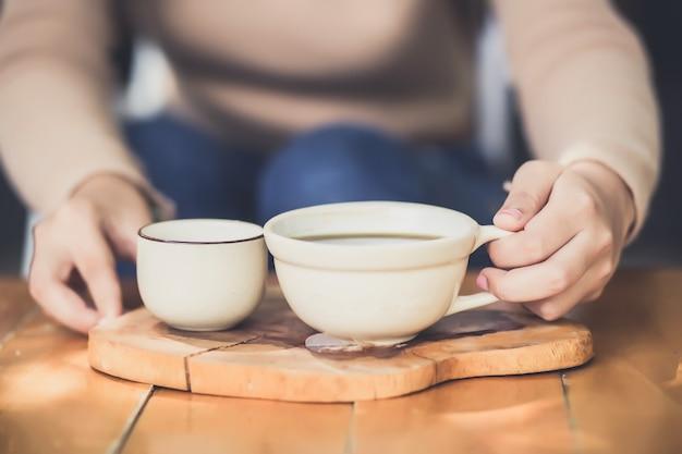 Jovem mulher segurando uma xícara de café quente na vista da natureza