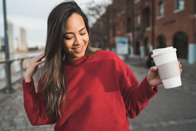 Jovem mulher segurando uma xícara de café.