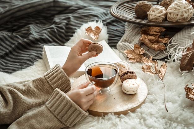 Jovem mulher segurando uma xícara de chá e um macaron