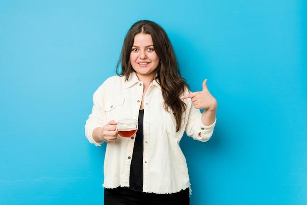 Jovem mulher segurando uma xícara de chá pessoa apontando à mão para uma camisa