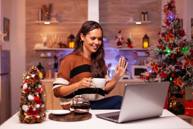 Jovem mulher segurando uma xícara de chá usando o conceito de videochamada