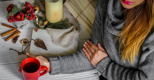 Jovem mulher segurando uma xícara de chá vermelha no quarto