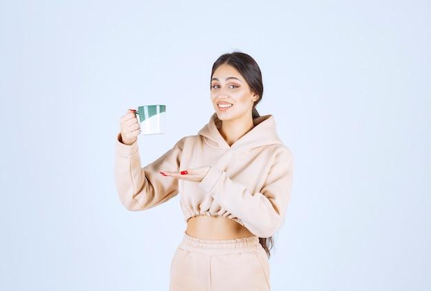 Jovem mulher segurando uma xícara verde de chá ou café