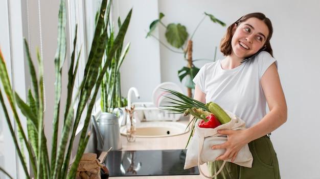 Jovem mulher segurando vegetais biológicos