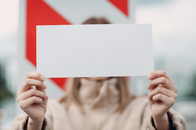 Jovem mulher segurar o cartaz do livro branco na mão. menina com folha de modelo em branco branco nas mãos.