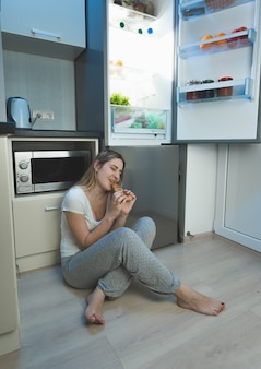 Jovem mulher sem dormir sentada no chão da cozinha ao lado de uma geladeira aberta e comendo pizza