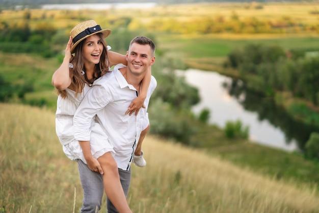 Jovem mulher sendo carregada pelo namorado no campo de grama. casal se divertindo nas férias de verão.