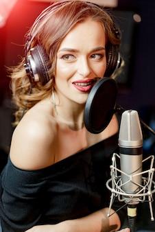 Jovem mulher sensual em roupas pretas com microfone e fones de ouvido.