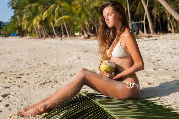 Jovem mulher sensual em trajes de banho de biquíni branco segurando coco, sorrindo, tomando banho de sol numa praia tropical.
