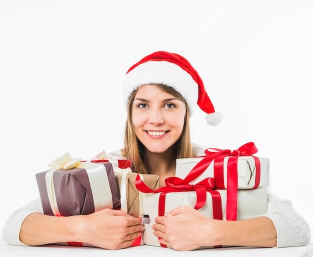 Jovem mulher sentada à mesa com caixas de presente