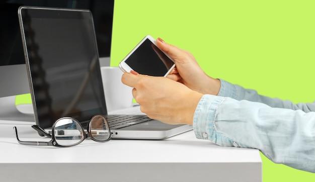 Jovem mulher sentada à mesa com o computador netbook aberto.
