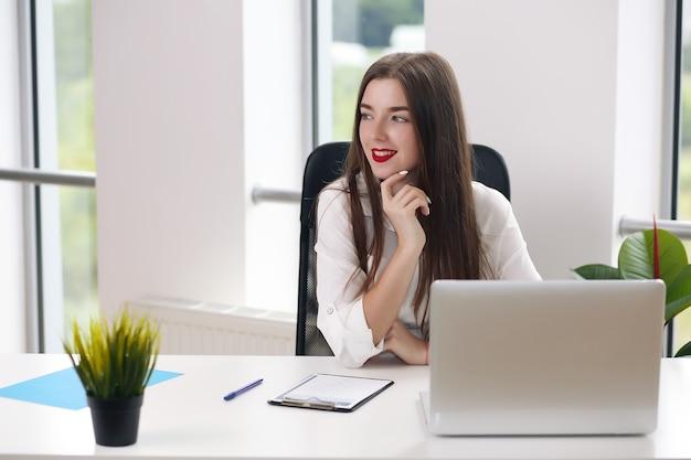 Jovem mulher sentada à mesa com um laptop em um escritório branco. estudante ou mulher de negócios.