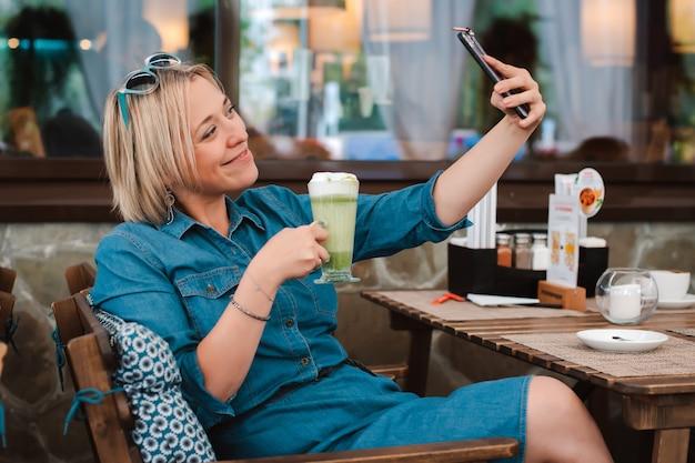 Jovem mulher sentada à mesa de um café de verão, bebendo uma bebida matcha verde e fazendo selfie