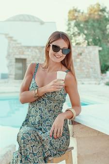 Jovem mulher sentada ao lado da piscina