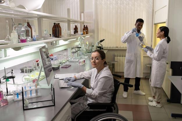 Jovem mulher sentada ao lado do computador contra dois colegas interculturais testando uma nova vacina