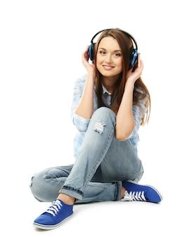 Jovem mulher sentada com fones de ouvido isolados no branco