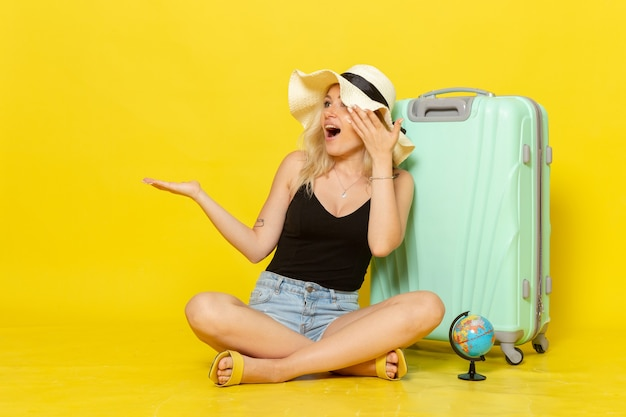 Jovem mulher sentada com sua bolsa no chão amarelo viagem férias viagem mar jornada sol