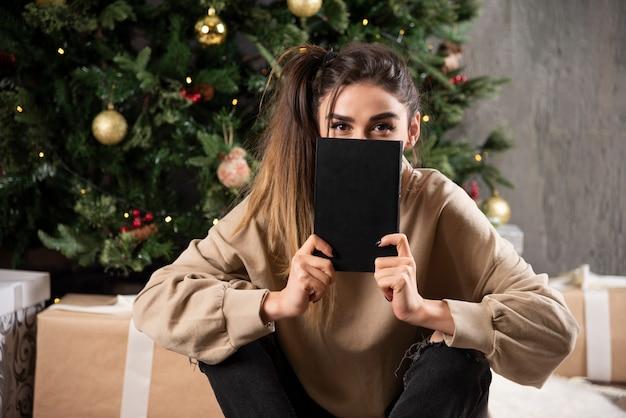 Jovem mulher sentada com um caderno preto perto da árvore de natal.