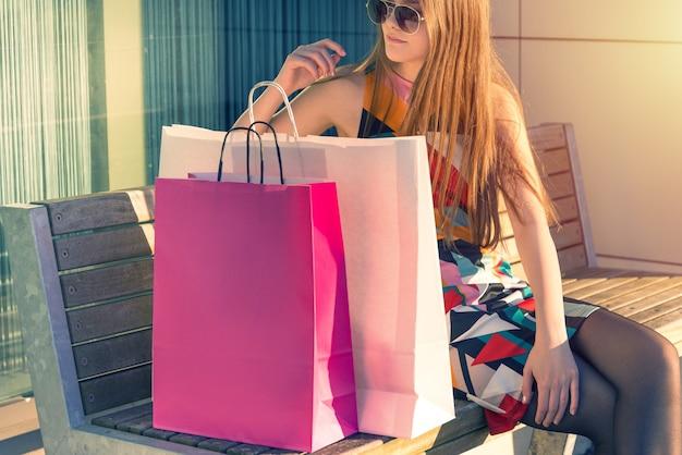 Jovem mulher sentada com uma sacola de compras