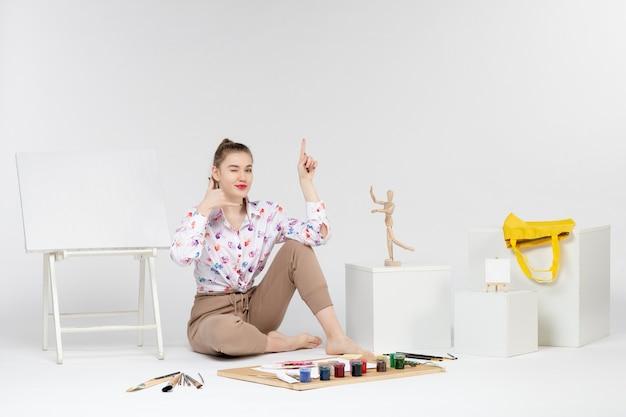 Jovem mulher sentada de frente com cavalete de tintas e pincéis em fundo branco