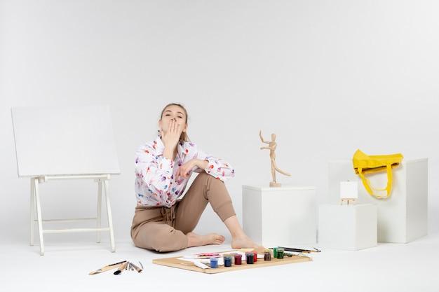 Jovem mulher sentada de frente com o cavalete de tintas e pincéis mandando beijos no fundo branco