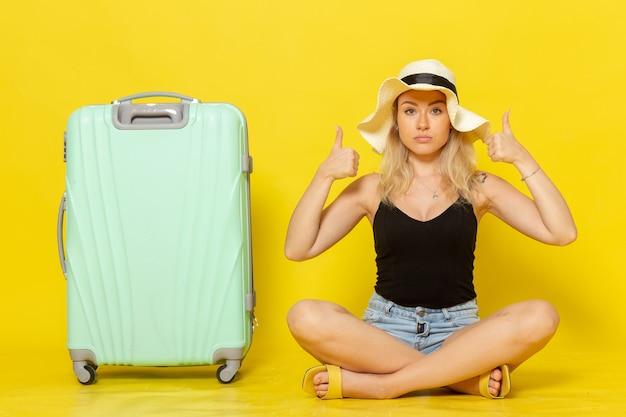 Jovem mulher sentada de frente com sua bolsa verde na parede amarela viagem férias sol viagem viagem garota