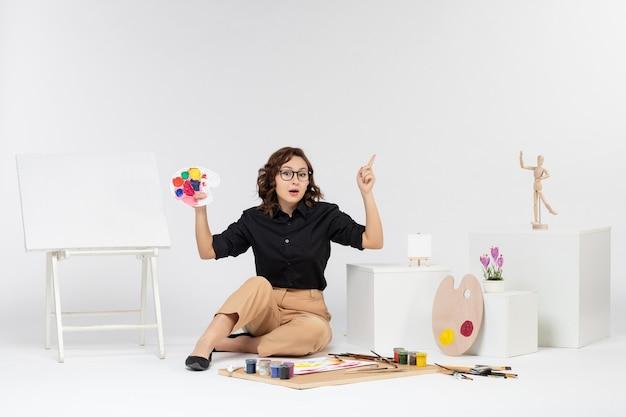 Jovem mulher sentada de frente com tintas e cavalete em fundo branco