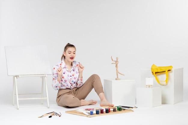 Jovem mulher sentada de frente com tintas e cavalete para desenhar em fundo branco