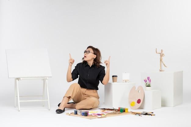 Jovem mulher sentada de frente na sala com cavalete e tintas em fundo branco